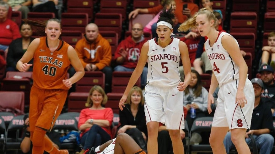 Stanford guard Lili Thompson, left, and Texas guard Ariel Atkins hit the ground after colliding during overtime of an NCAA college basketball game in Stanford, Calif., Thursday, Nov. 20, 2014. Texas defeated Stanford 87-81.(AP Photo/Beck Diefenbach)