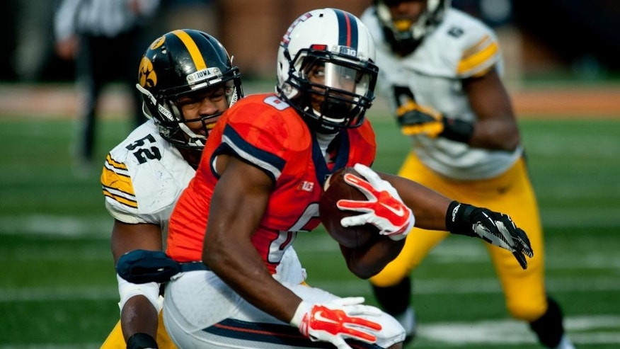 Illinois running back Josh Ferguson (6) tries to avoid a tackle by Iowa linebacker Quinton Alston (52) during the fourth quarter of an NCAA football game Saturday, Nov. 15, 2014, at Memorial Stadium in Champaign, Ill. (AP Photo/Bradley Leeb)