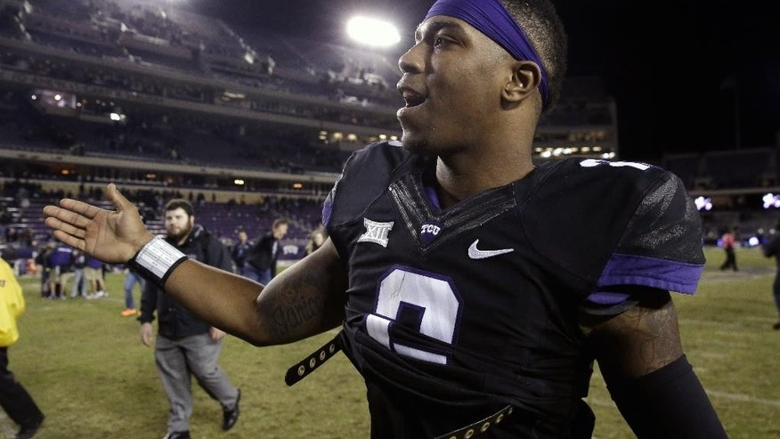 FILE - In this Nov. 8, 2014, file photo, TCU quarterback Trevone Boykin is congratulated as he walks off the field after an NCAA college football game against Kansas State in Fort Worth, Texas. Boykin, the only TCU player ever with a 200-yard passing game, 100-yard receiving game and 100-yard rushing game in the same season is now focused only on being the quarterback in TCU's new up-tempo offense, with the No. 5 Horned Frogs in playoff contention and him in the Heisman conversation. (AP Photo/LM Otero, File)