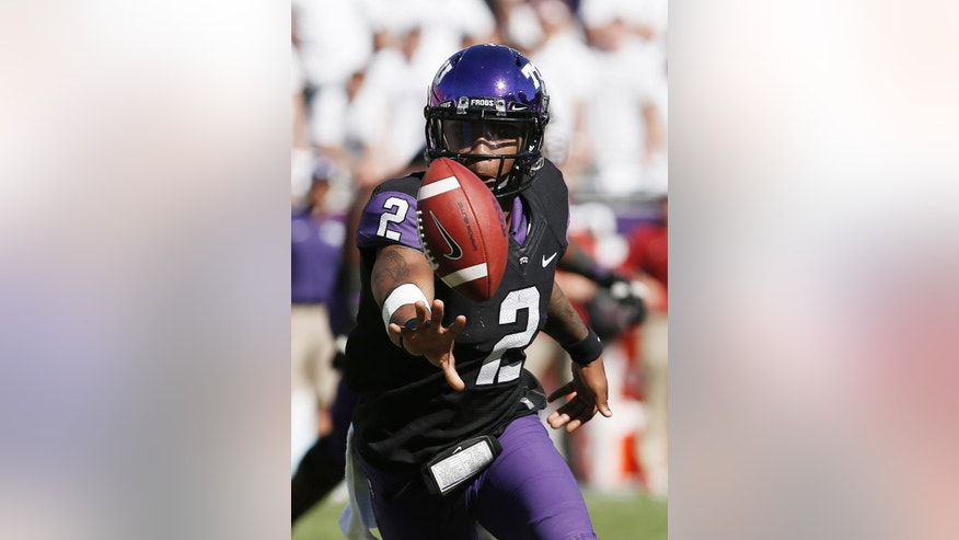 FILE - In this Oct. 4, 2014, file photo, TCU quarterback Trevone Boykin (2) pitches the ball to a teammate during the first half of a NCAA college football game against Oklahoma in Fort Worth, Texas. The only TCU player ever with a 200-yard passing game, 100-yard receiving game and 100-yard rushing game in the same season is now focused only on being the quarterback in TCU's new up-tempo offense, with the No. 5 Horned Frogs in playoff contention and him in the Heisman conversation. (AP Photo/Brandon Wade, File)