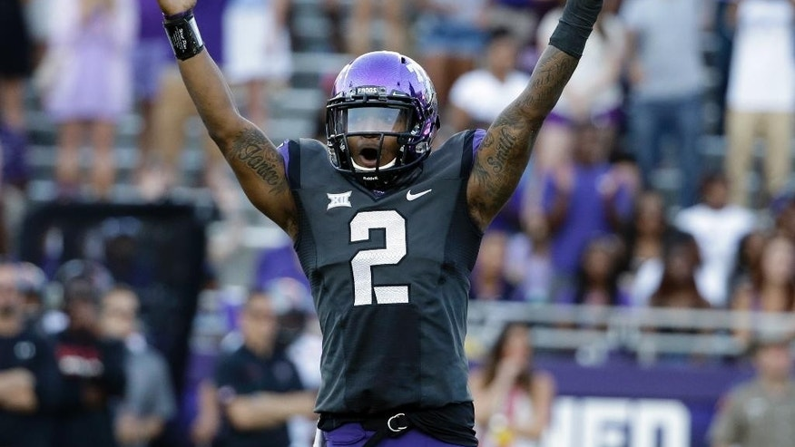 FILE - In this Oct. 25, 2014, file photo, TCU quarterback Trevone Boykin (2) celebrates a score against Texas Tech in the second half of an NCAA college football game in Fort Worth, Texas. The only TCU player ever with a 200-yard passing game, 100-yard receiving game and 100-yard rushing game in the same season is now focused only on being the quarterback in TCU's new up-tempo offense, with the No. 5 Horned Frogs in playoff contention and him in the Heisman conversation. (AP Photo/Tony Gutierrez, File0