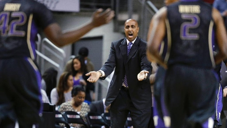 Washington coach Lorenzo Romar, center, calls to his team during the first half of an NCAA college basketball game against Seattle on Friday, Nov. 21, 2014, in Seattle. (AP Photo/Ted S. Warren)