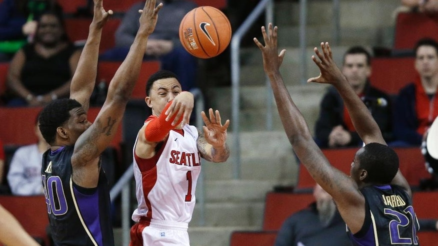 Seattle's Isiah Umipig (1) passes between Washington's Shawn Kemp Jr., left, and Jernard Jarreau during the first half of an NCAA college basketball game, Friday, Nov. 21, 2014, in Seattle. (AP Photo/Ted S. Warren)