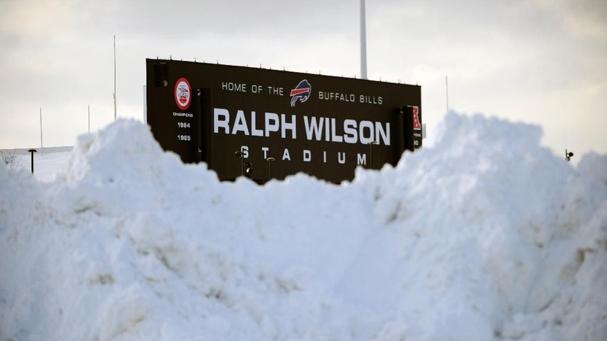 """Huge snowbanks almost obscure the Ralph Wilson Stadium sign above the stadium in Orchard Park, N.Y. Friday, Nov. 21, 2014. Snowed out in Buffalo, the Bills are heading to Detroit to play their """"home"""" NFL football game against the New York Jets on Monday night, Nov. 24, 2014. (AP Photo/Gary Wiepert)"""