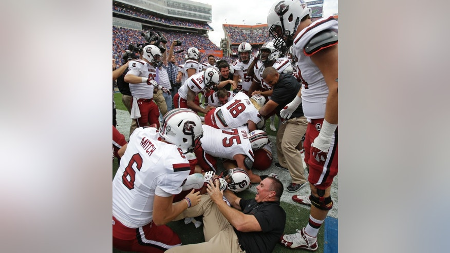 South Carolina players and coaches celebrate as they pile on quarterback Dylan Thompson, not seen, after he scored the game-winning touchdown in overtime to defeat Florida 23-20 in an NCAA college football game in Gainesville, Fla., Saturday, Nov. 15, 2014. (AP Photo/John Raoux)