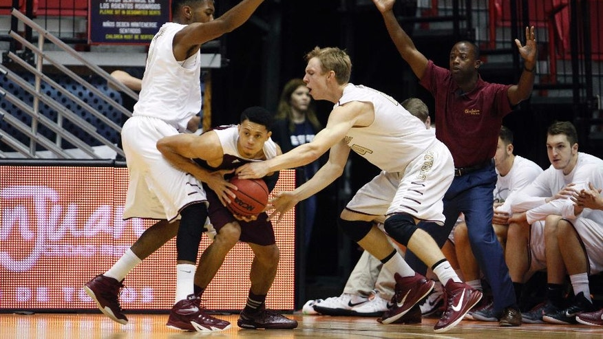 College of Charleston guard Canyon Barry, right, and teammate forward Donovan Gilmore, left, pressures Texas A&M guard Jordan Green, center, as Texas A&M head coach Billy Kennedy gestures, behind, during a NCAA college basketball game in San Juan, Puerto Rico, Friday, Nov. 21, 2014. (AP Photo/Ricardo Arduengo)