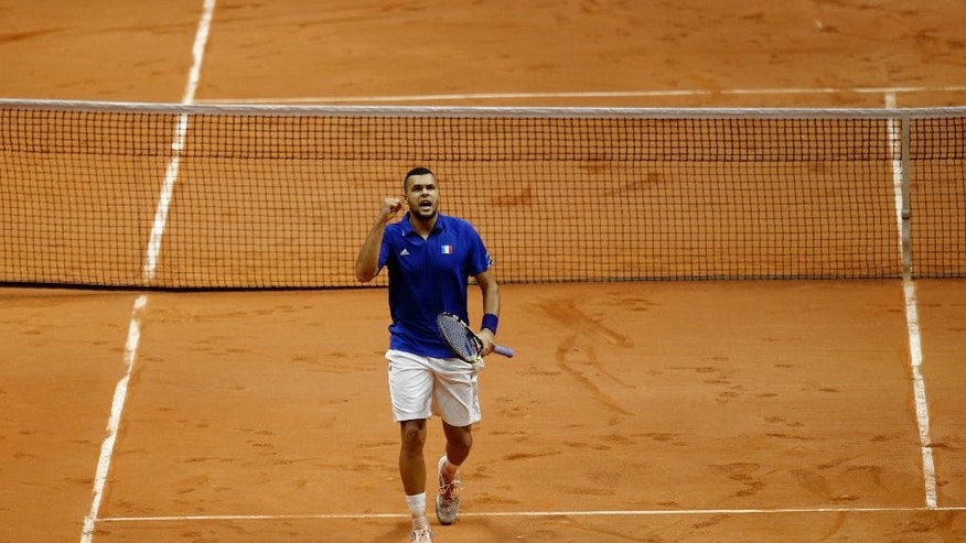 France's Jo-Wilfried Tsonga reacts after a winning point as he plays Switzerland's Stanislas Wawrinka during the  Davis Cup final in Lille, northern France, Friday, Nov.21, 2014. Switzerland is seeking a first victory in the team competition while France is looking for a 10th title. This is the 13th meeting between the two nations, with France leading 10-2. (AP Photo/Peter Dejong)