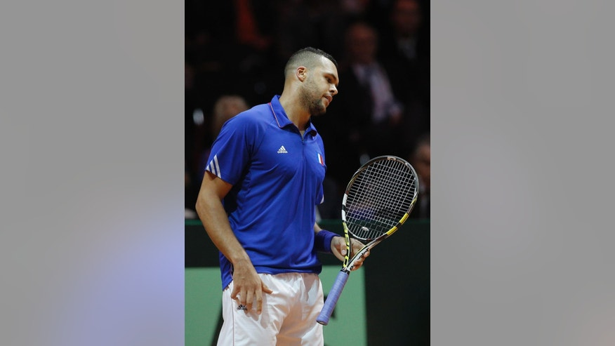 France's Jo-Wilfried Tsonga reacts as he plays Switzerland's Stanislas Wawrinka during the Davis Cup final in Lille, northern France, Friday, Nov.21, 2014. Switzerland is seeking a first victory in the team competition while France is looking for a 10th title. This is the 13th meeting between the two nations, with France leading 10-2. (AP Photo/Christophe Ena)