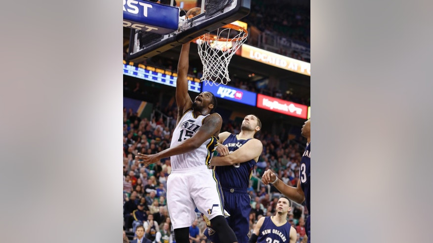 Utah Jazz forward Derrick Favors (15) hits a shot while defended by New Orleans Pelicans forward Ryan Anderson (33) during the second half of their NBA Basketball game in Salt Lake City, Utah, Saturday, Nov. 22, 2014. The New Orleans Pelicans won 106 - 94. (AP Photo/Jim Urquhart)