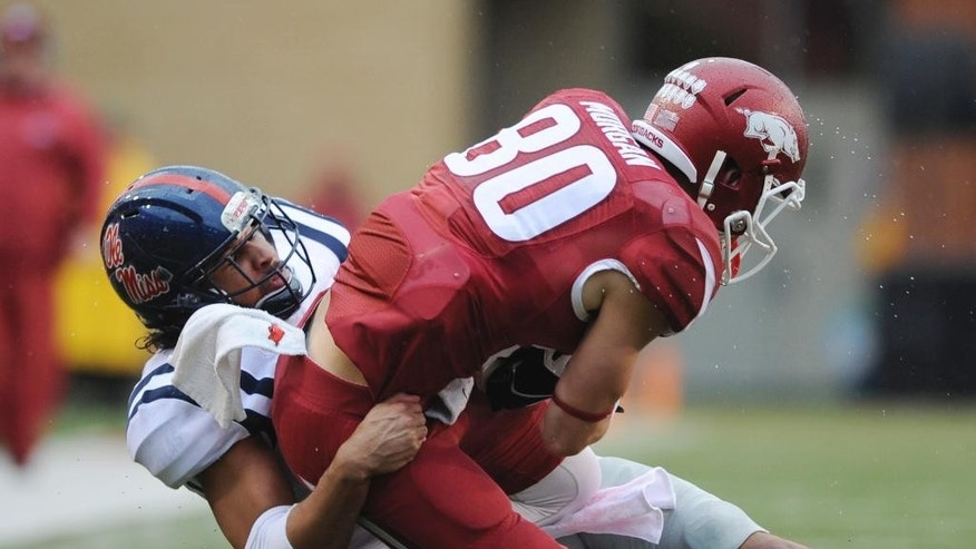 Mississippi defensive back Cody Prewitt, left, brings down Arkansas wide receiver Drew Morgan (80) in the second quarter of an NCAA college football game Saturday, Nov. 22, 2014, in Fayetteville, Ark. (AP Photo/Sarah Bentham)