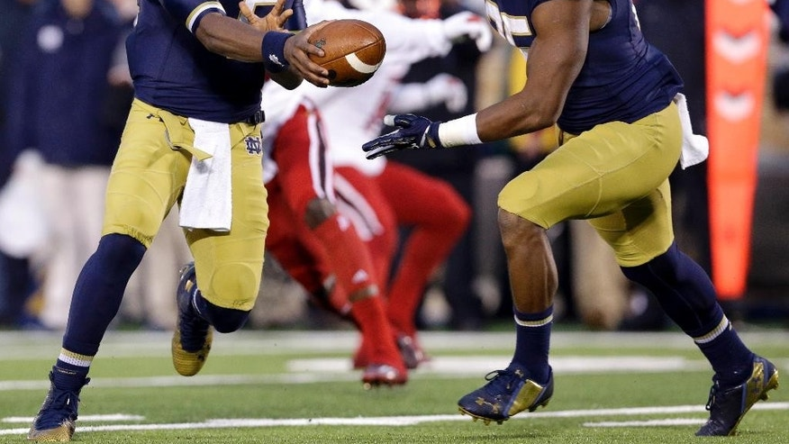 Notre Dame quarterback Everett Golson (5) hands off the ball to running back Tarean Folston, right, during the first half of an NCAA college football game against Louisville in South Bend, Ind., Saturday, Nov. 22, 2014. (AP Photo/Nam Y. Huh)