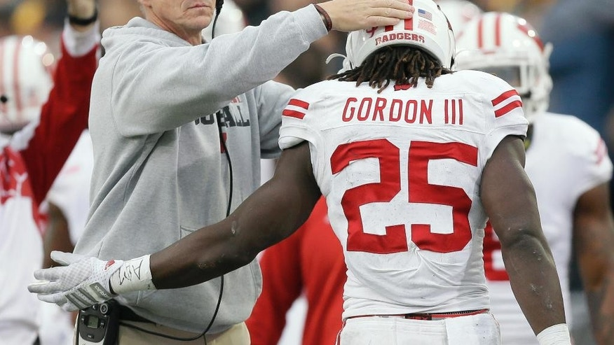 Wisconsin running back Melvin Gordon (25) celebrates with head coach Gary Andersen, left, after scoring on a 6-yard touchdown run during the first half of an NCAA college football game against Iowa, Saturday, Nov. 22, 2014, in Iowa City, Iowa. (AP Photo/Charlie Neibergall)