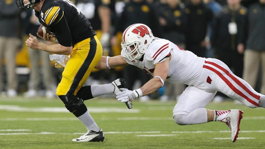 Iowa quarterback Jake Rudock, left, runs from Wisconsin linebacker Vince Biegel, right, during the first half of an NCAA college football game, Saturday, Nov. 22, 2014, in Iowa City, Iowa. (AP Photo/Charlie Neibergall)
