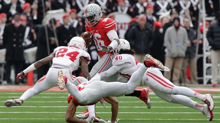 Ohio State quarterback J.T. Barrett, top, tries to run to the outside as Indiana cornerback Danny Dunn, left, and safety Antonio Allen defend during the first quarter of an NCAA college football game Saturday, Nov. 22, 2014, in Columbus, Ohio. (AP Photo/Jay LaPrete)