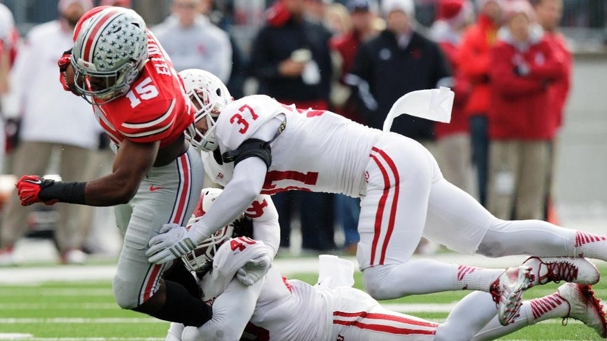 Ohio State running back Ezekiel Elliott, left, is tackled by Indiana defenders Mark Murphy, top, and Antonio Allen during the first quarter of an NCAA college football game Saturday, Nov. 22, 2014, in Columbus, Ohio. (AP Photo/Jay LaPrete)