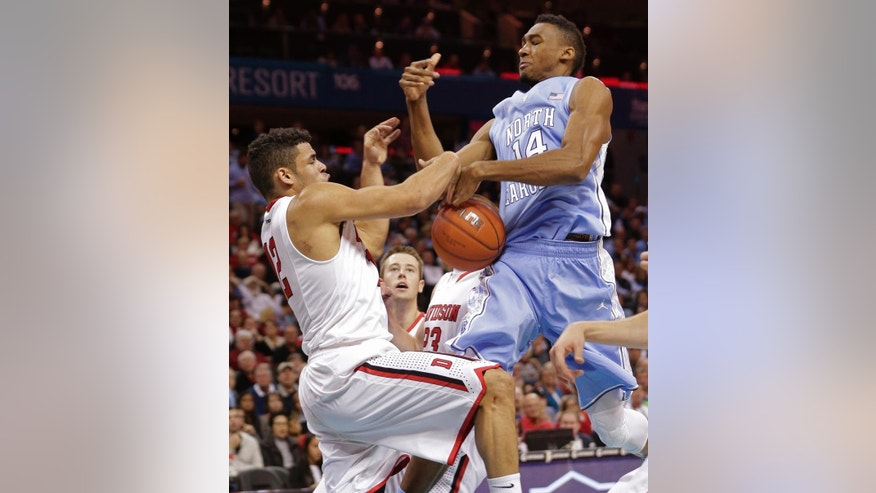 North Carolina's Desmond Hubert (14) and Davidson's Jack Gibbs (12) battle for a rebound during the first half of an NCAA college basketball game in Charlotte, N.C., Saturday, Nov. 22, 2014. (AP Photo/Chuck Burton)