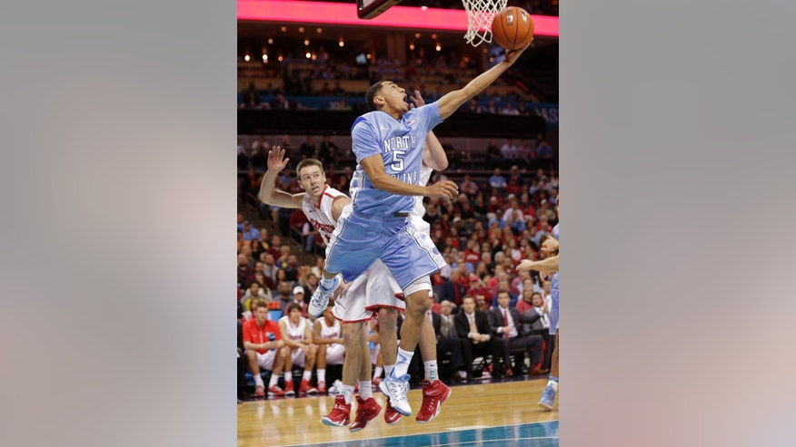 North Carolina's Marcus Paige (5) drives past Davidson's Tyler Kalinoski, left, during the first half of an NCAA college basketball game in Charlotte, N.C., Saturday, Nov. 22, 2014. (AP Photo/Chuck Burton)