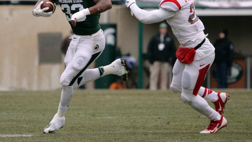 Michigan State's Jeremy Langford (33) escapes from Rutgers' Delon Stephenson en route to a 38-yard rushing touchdown during the second quarter of an NCAA college football game, Saturday, Nov. 22, 2014, in East Lansing, Mich. (AP Photo/Al Goldis)