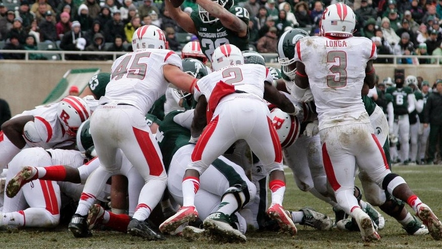 Michigan State's Nick Hill (20) leaps over the pile for a touchdown against Rutgers' Kevin Snyder (45), Gareef Glashen (2) and Steve Longa (3) during the second quarter of an NCAA college football game, Saturday, Nov. 22, 2014, in East Lansing, Mich. (AP Photo/Al Goldis)