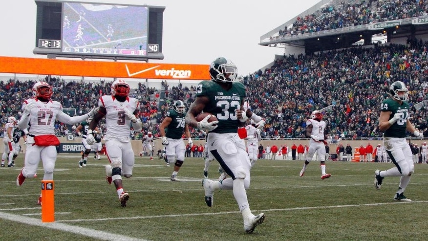 Michigan State's Jeremy Langford (33) scores a touchdown on a 38-yard run in front of Rutgers' Delon Stephenson (27) and Steve Longa (3) during the second quarter of an NCAA college football game, Saturday, Nov. 22, 2014, in East Lansing, Mich. (AP Photo/Al Goldis)