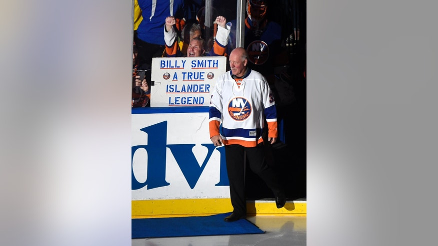 Former New York Islander Billy Smith enters the ice to drop the first ceremonial puck before an NHL hockey game between the Islanders and the Pittsburgh Penguins at Nassau Coliseum on Saturday, Nov. 22, 2014, in Uniondale, N.Y. Smith won four Stanley Cups with the Islanders. (AP Photo/Kathy Kmonicek)