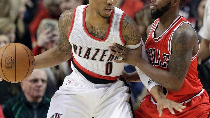 Chicago Bulls guard Aaron Brooks, right, defends Portland Trail Blazers guard Damian Lillard during the first half of an NBA basketball game in Portland, Ore., Friday, Nov. 21, 2014.(AP Photo/Don Ryan)