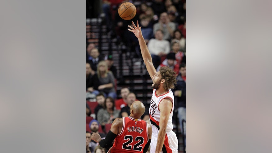 Portland Trail Blazers center Robin Lopez, right, shoots over Chicago Bulls forward Taj Gibson during the first half of an NBA basketball game  in Portland, Ore., Friday, Nov. 21, 2014.(AP Photo/Don Ryan)