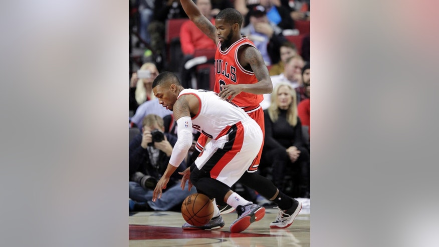 Portland Trail Blazers guard Damian Lillard, left, loses control of the ball as Chicago Bulls guard Aaron Brooks defends during the first half of an NBA basketball game in Portland, Ore., Friday, Nov. 21, 2014.(AP Photo/Don Ryan)