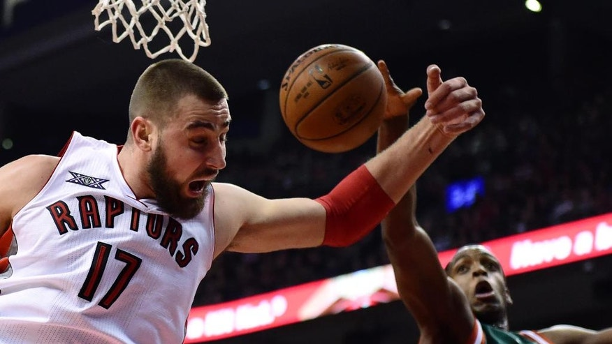 Toronto Raptors' Jonas Valanciunas, left, and Milwaukee Bucks' Khris Middleton battle for a loose ball under the basket during first-half NBA basketball game action in Toronto, Friday, Nov. 21, 2014. (AP Photo/The Canadian Press, Frank Gunn)