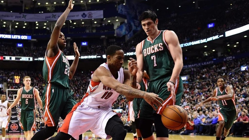 Toronto Raptors' DeMar DeRozan, center, makes a pass for an assist as Milwaukee Bucks' Ersan Ilyasova (7) defends during first-half NBA basketball game action in Toronto, Friday, Nov. 21, 2014. (AP Photo/The Canadian Press, Frank Gunn)