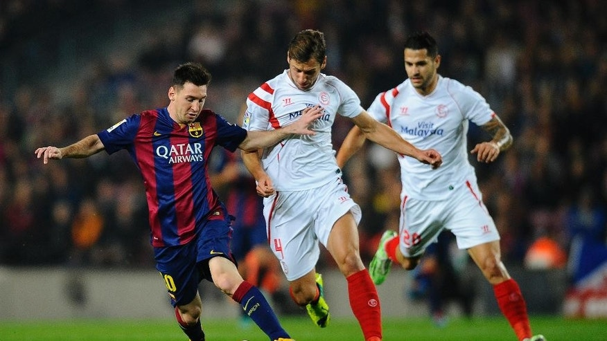 FC Barcelona's Lionel Messi, left, duels for the ball against Sevilla's Grzegorz Krychowiak, center, during a Spanish La Liga soccer match at the Camp Nou stadium in Barcelona, Spain, Saturday, Nov. 22, 2014. (AP Photo/Manu Fernandez)