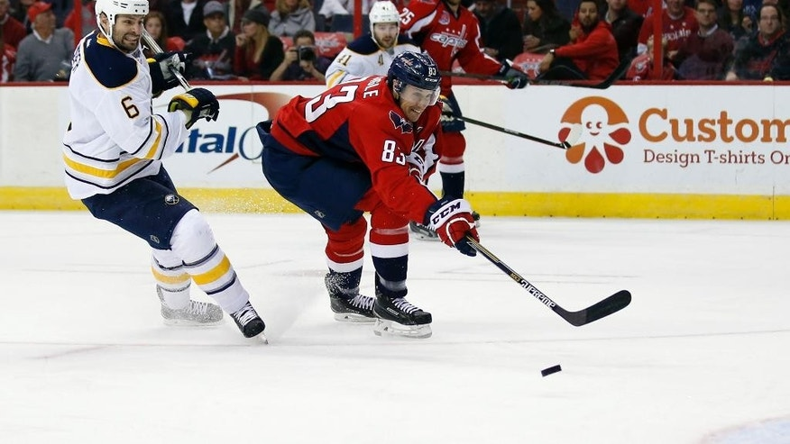 Washington Capitals center Jay Beagle (83) can't reach a pass with Buffalo Sabres defenseman Mike Weber (6) behind him, in the first period of an NHL hockey game, Saturday, Nov. 22, 2014, in Washington. (AP Photo/Alex Brandon)
