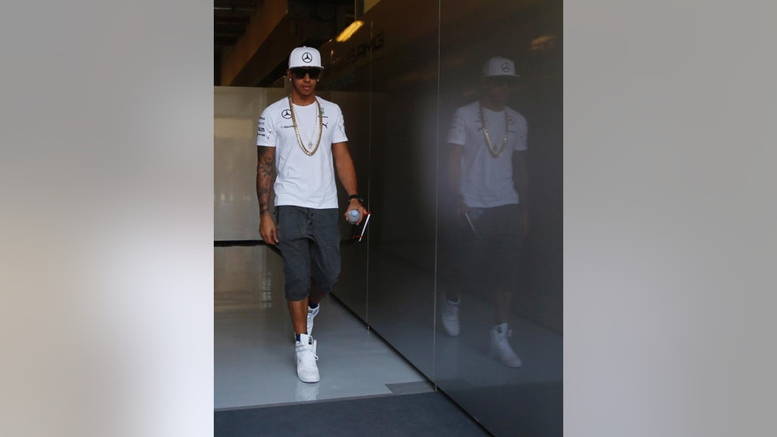 Mercedes driver Lewis Hamilton of Britain walks in the paddock prior to the start of the third free practice at the Yas Marina racetrack in Abu Dhabi, United Arab Emirates, Saturday, Nov. 22, 2014. With double points on offer in the Formula One finale, there could yet be a bitter twist to the fascinating title duel between Mercedes teammates Lewis Hamilton and Nico Rosberg at the Abu Dhabi Grand Prix. The Emirates Formula One Grand Prix will take place on Sunday. (AP Photo/Luca Bruno)