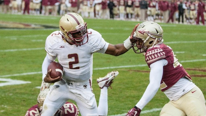 Boston College quarterback Tyler Murphy, center, gets sacked by Florida State defenders Lamarcus Brutus, right, and Nate Andrews, in the first half of an NCAA college football game in Tallahassee, Fla., Saturday, Nov. 22, 2014.  (AP Photo/Mark Wallheiser)