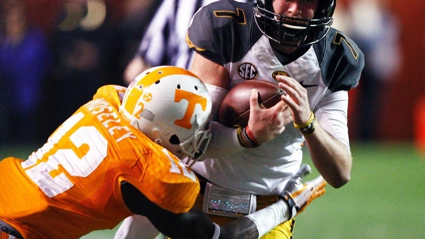 Missouri quarterback Maty Mauk (7) runs for yardage as he's hit by Tennessee defensive back Emmanuel Moseley (12) in the first half of an NCAA college football game Saturday, Nov. 22, 2014, in Knoxville, Tenn. (AP Photo/Wade Payne)
