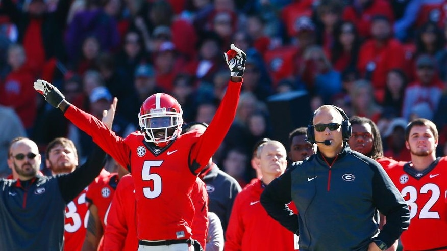 Georgia head coach Mark Richt, right. and cornerback Damian Swann (5) watch as Georgia makes a field goal during the first half of an NCAA college football game against Charleston Southern, Saturday, Nov. 22, 2014, in Athens, Ga.   (AP Photo/John Bazemore)