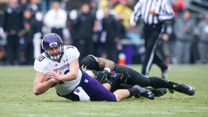 Northwestern's Zack Oliver (10) grimaces as he's brought down by Purdue's Ryan Russell (99) during the first half of an NCAA college football game, Saturday, Nov. 22, 2014, in West Lafayette, Ind. (AP Photo/Doug McSchooler)