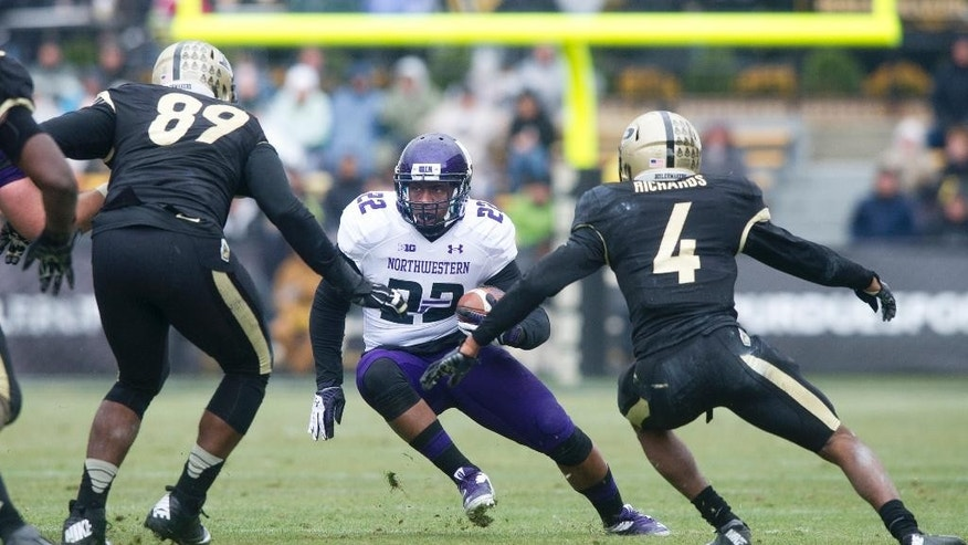 Northwestern's Treyvon Green (22) is stopped by Purdue's Jalani Phillips (89) and Taylor Richards (4) as he runs the ball during the first half of an NCAA college football game, Saturday, Nov. 22, 2014, in West Lafayette, Ind. (AP Photo/Doug McSchooler)