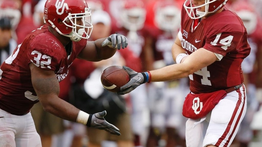Oklahoma's Cody Thomas (14) hands off to teammate Samaje Perine (32) in the second quarter of an NCAA college football game against Kansas in Norman, Okla., Saturday, Nov. 22, 2014. (AP Photo/Sue Ogrocki)