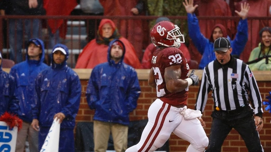 Oklahoma's Samaje Perine (32) runs into the end zone past the Kansas cheerleaders for a touchdown in the first quarter of an NCAA college football game against Kansas in Norman, Okla., Saturday, Nov. 22, 2014. (AP Photo/Sue Ogrocki)