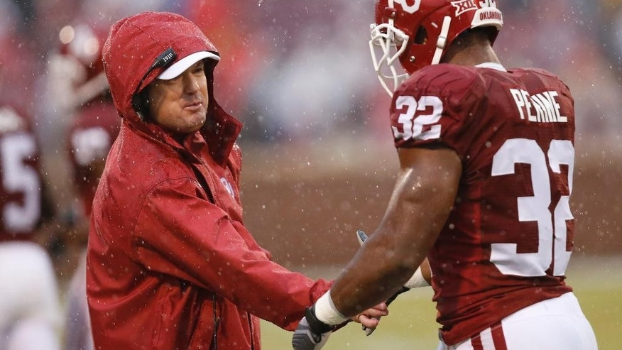 Oklahoma head coach Bob Stoops, left, congratulates Samaje Perine (32) following his touchdown against Kansas in the first quarter of an NCAA college football game in Norman, Okla., Saturday, Nov. 22, 2014. (AP Photo/Sue Ogrocki)