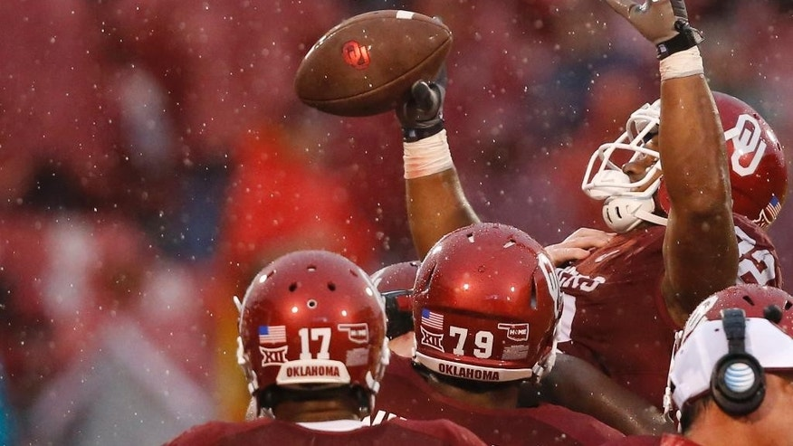 Oklahoma's Samaje Perine, right, is lifted up by his teammates in the fourth quarter, after breaking the NCAA FBS single-game rushing record of 408 yards, set last week by Melvin Gordon, with 427 yards in an NCAA college football game against Kansas in Norman, Okla., Saturday, Nov. 22, 2014. Oklahoma won 44-7. (AP Photo/Sue Ogrocki)