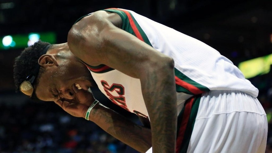 Milwaukee Bucks center Larry Sanders holds his temple after getting hit in the head during play against the Washington Wizards during the first half of an NBA basketball game, Saturday, Nov. 22, 2014, in Milwaukee. (AP Photo/Darren Hauck)