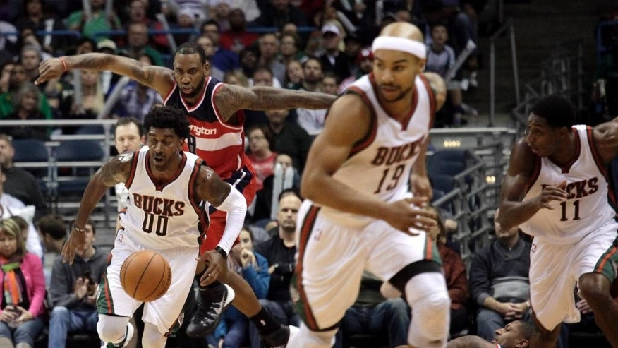 Milwaukee Bucks guard O.J. Mayo, left, steals the ball from Washington Wizards guard Bradley Beal, back right, during the second half of an NBA basketball game, Saturday, Nov. 22, 2014, in Milwaukee. (AP Photo/Darren Hauck)