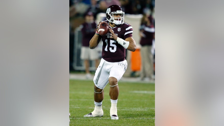 Mississippi State quarterback Dak Prescott (15) looks for an open man to pass to against Vanderbilt in the first half of an NCAA college football game Saturday, Nov. 22, 2014, in Starkville, Miss. (AP Photo/Rogelio V. Solis)