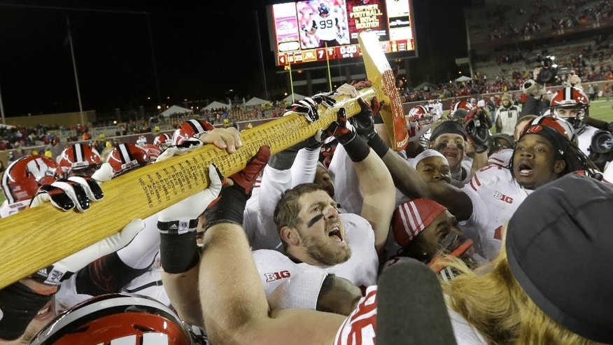FILE - In this Nov. 23, 2013, file photo, Wisconsin linebacker Conor O'Neill, center, carries Paul Bunyan's Axe after Wisconsin beat Minnesota 20-7 in an NCAA college football game in Minneapolis. Ahead of the college football season, The Associated Press asked its panel of voters in the Top 25 poll to weigh in on the best traveling trophies in college football. Three that the Gophers play for grabbed the tops spots, starting with Paul Bunyan's Axe, which Wisconsin and Minnesota will play for on Thanksgiving weekend. (AP Photo/Ann Heisenfelt, File)