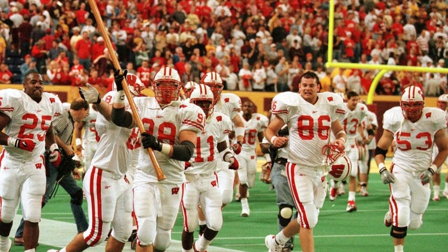 FILE - In this Oct. 9, 1999, file photo, Wisconsin's Mark Neuser (98) carries Paul Bunyan's Axe as he and his Badger teammates circle the field after beating Minnesota in overtime 20-17 in Minneapolis. Ahead of the college football season, The Associated Press asked its panel of voters in the Top 25 poll to weigh in on the best traveling trophies in college football. Three that the Gophers play for grabbed the tops spots, starting with Paul Bunyan's Axe, which Wisconsin and Minnesota will play for on Thanksgiving weekend. (AP Photo/Paul Battaglia, File)