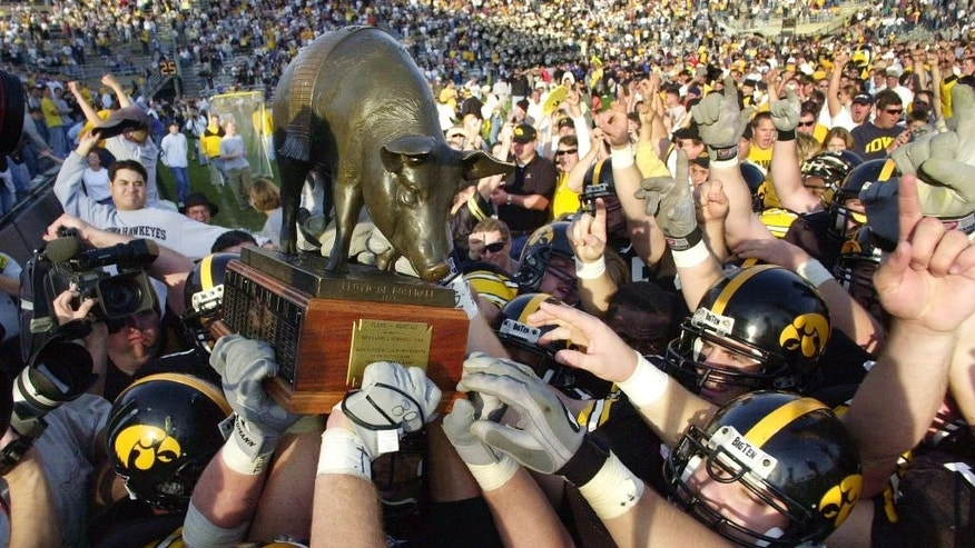 FILE - In this Nov. 17, 2001, file photo, Iowa players hoist the Floyd of Rosedale trophy after defeating Minnesota 42-24 in Iowa City, Iowa. Ahead of the college football season, The Associated Press asked its panel of voters in the Top 25 poll to weigh in on the best traveling trophies in college football. Three that the Gophers play for grabbed the tops spots. (AP Photo/Charlie Neibergall, File)