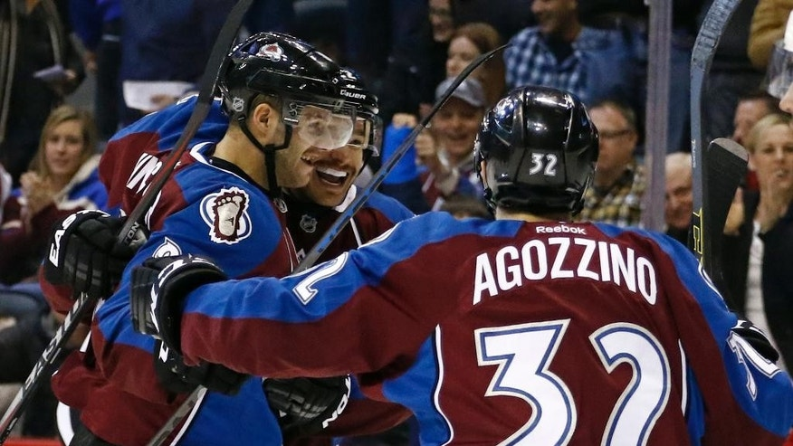 Colorado Avalanche defenseman Zach Redmond, rear is congratulated by teammates Tomas Vincour, front left, and Andrew Agozzino (32) after scoring a goal against the Carolina Hurricanes during the first period of an NHL hockey game Saturday, Nov. 22, 2014, in Denver. (AP Photo/Jack Dempsey)