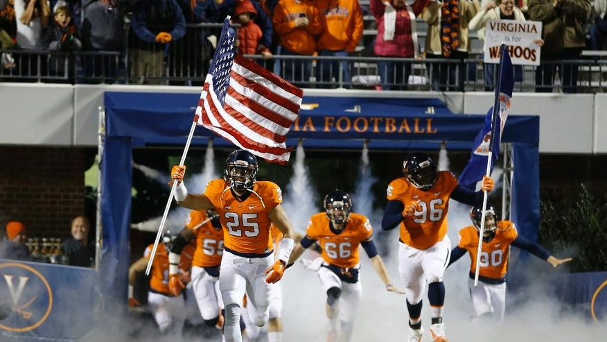 Virginia running back Kevin Parks (25) carries a United States flag as the team comes onto the field for an NCAA college football game against Miami in Charlottesville, Va., Saturday, Nov. 22, 2014. (AP Photo/Steve Helber)
